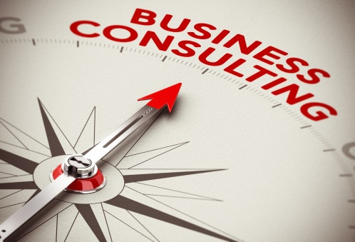 Realistic concept of strategic business. Compass needle pointing the red word business consulting over a paper background